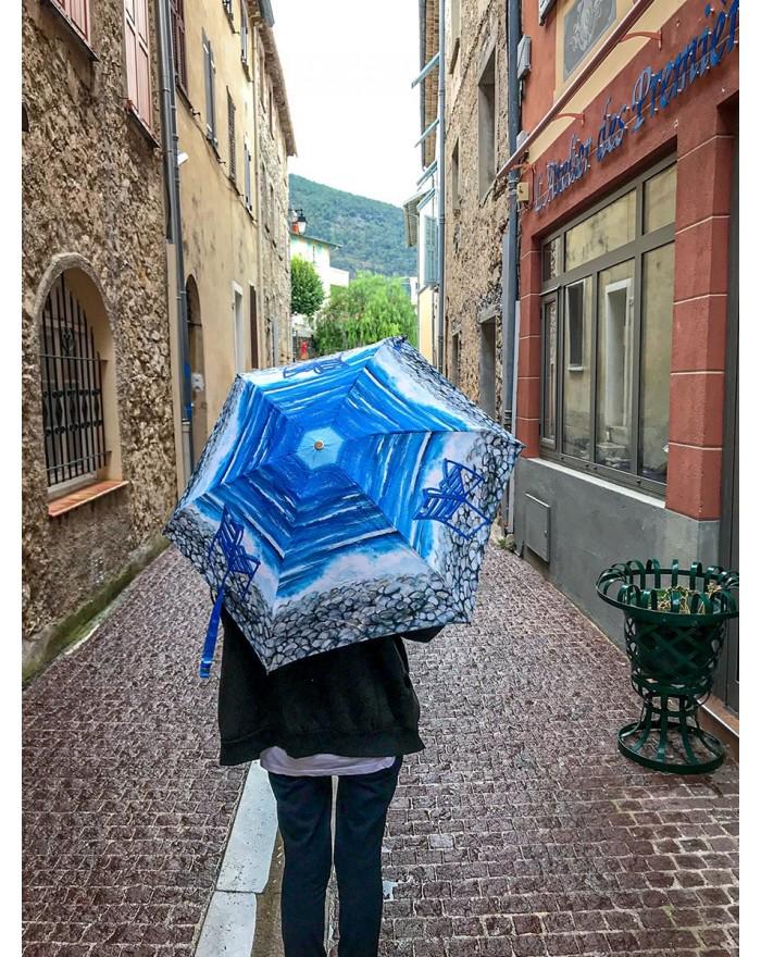 Parapluie pliant Chaise Bleue sur galet devant le magasin de l'Atelier des premières Chaises Bleues à Tourrette-Levens.